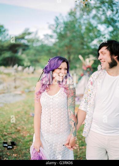 Sweden, Bride and groom standing holding hands at hippie wedding - Stock Image