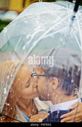 Young couple kissing under the umbrella - Stock-Bilder