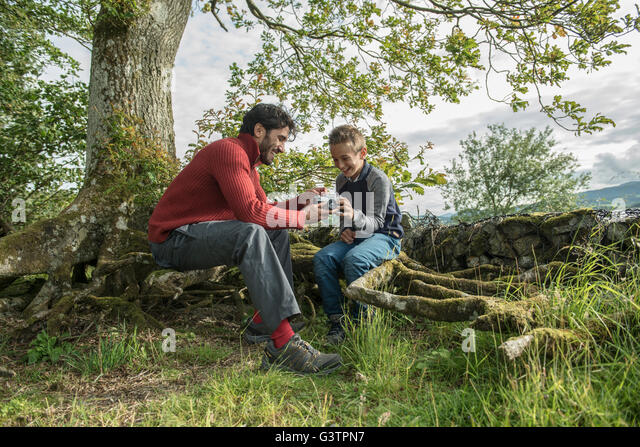 A man showing his son how to use a camera on the shore of Bala Lake in Wales. - Stock Image
