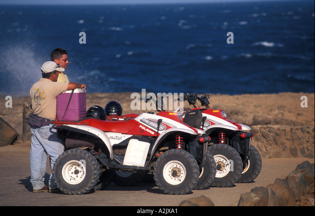 Aruba Tourist and Guide dune buggy Riding ATVs in desert - Stock Image