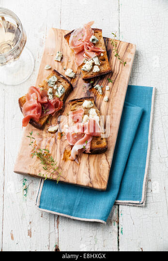 Bruschettas with Blue cheese and ham on grilled crusty bread on blue wooden background - Stock Image