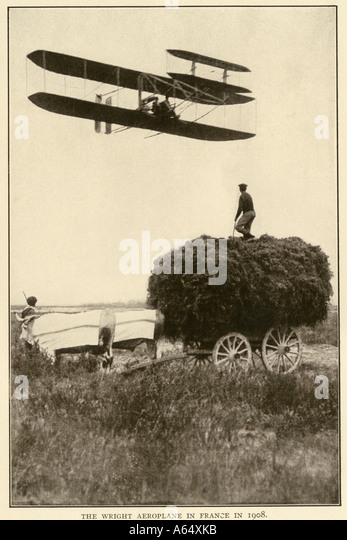 Wilbur Wright and a pupil in an early airplane flying over an oxdrawn hay wagon in France 1908 - Stock Image