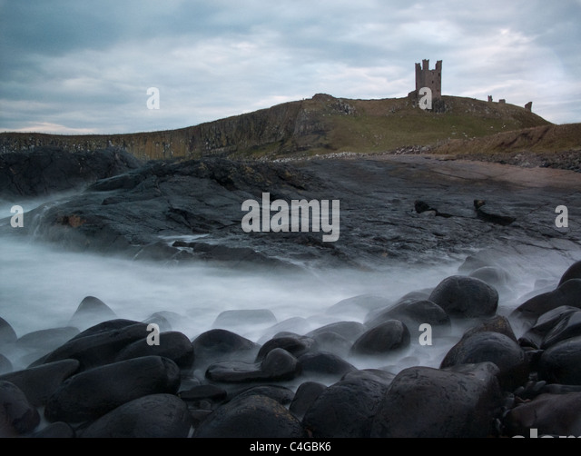 Sea rolling over rocks in front of Dunstanburgh Castle - Stock Image