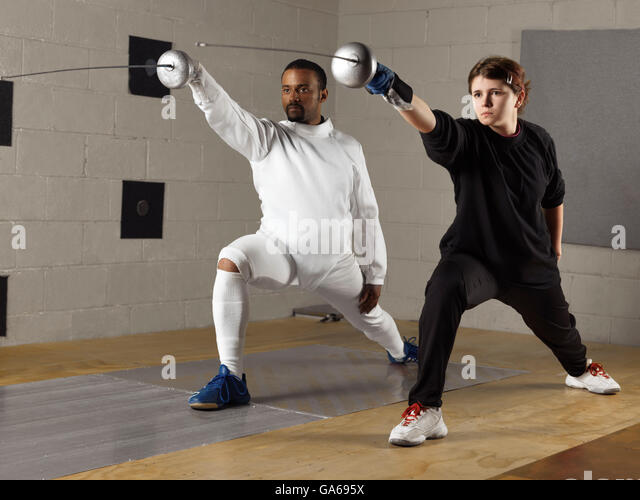 Coach and a teenage student practicing fencing in a gym - Stock Image