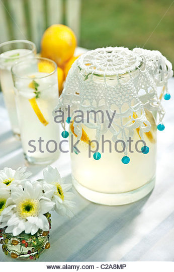 Jug of lemonade with crocheted beaded jug cover, drink tumblers, lemons and small vase of cut flowers - Stock Image