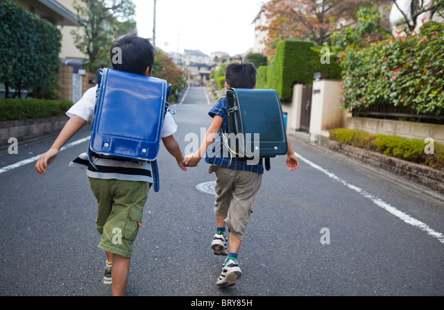 Boys holding hands and running, Tokyo Prefecture, Honshu, Japan - Stock Image