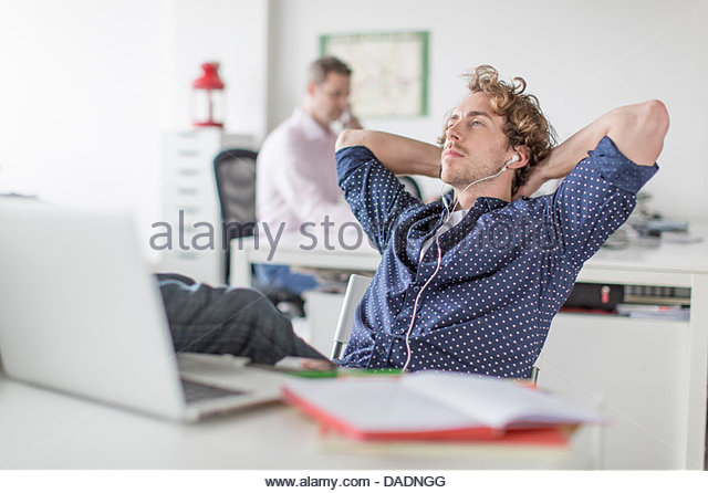 Young office worker reclining at desk with hands behind head - Stock-Bilder