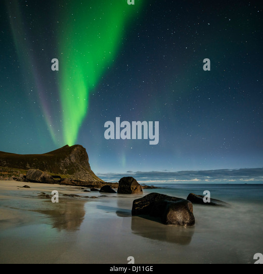 Northern Lights fill sky over Myrland beach, Flakstadoy, Lofoten Islands, Norway - Stock Image