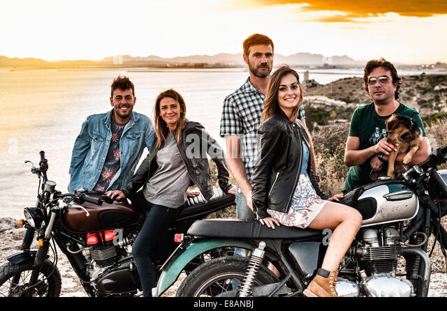 Portrait of five motorcycling friends on coast at sunset, Cagliari, Sardinia, Italy - Stock Image