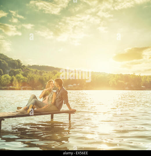 Couple in love sitting on the pier - Stock-Bilder