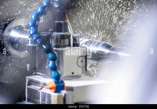 Water spraying on machinery in factory - Stock Image