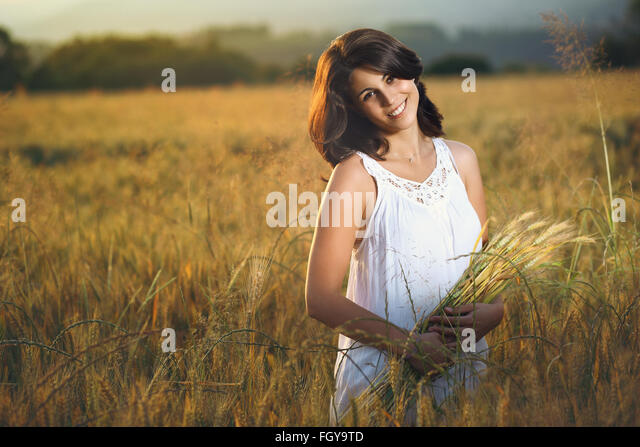 Beautiful smiling woman in a golden field at sunset. Summer season portrait - Stock-Bilder