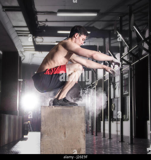Fit young man box jumping at a crossfit gym.Athlete is performin - Stock Image