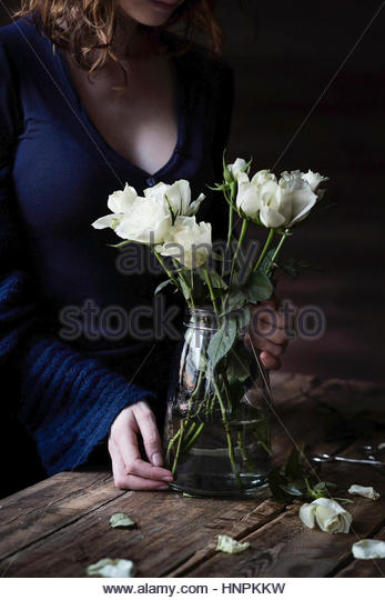 White roses on wooden table and woman on the background - Stock Image