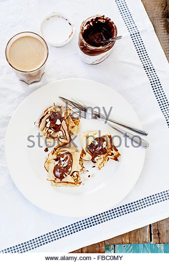 Pancakes with chocolate and coffee on white textile outdoor - Stock Image