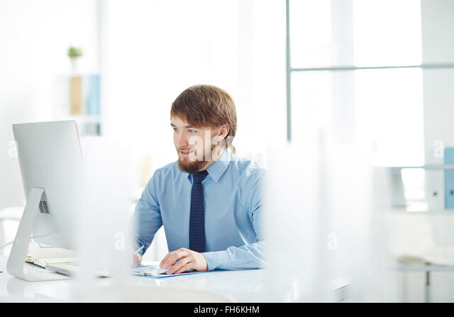 Contemporary businessman looking at monitor in office - Stock-Bilder