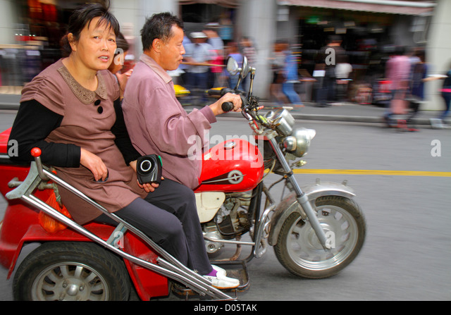 Shanghai China Huangpu District Sichuan Road Asian man woman motorcycle riding no helmet motion three-wheeled trike - Stock Image