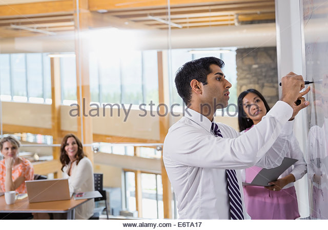 Businessman writing on white board in meeting - Stock-Bilder