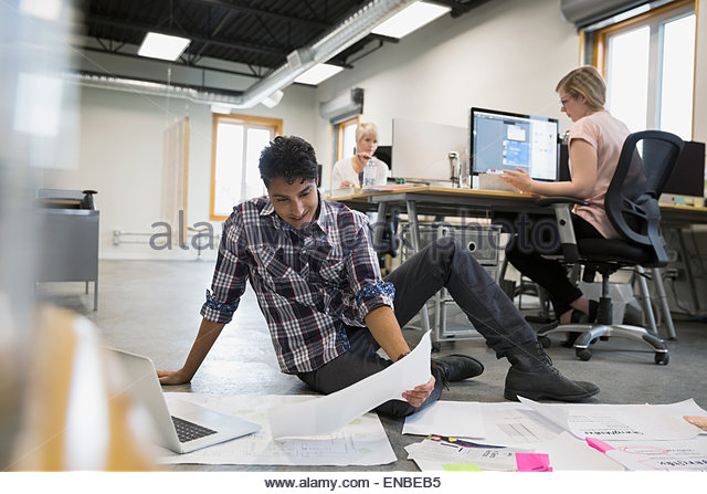 Graphic designer reviewing proofs on office floor - Stock-Bilder