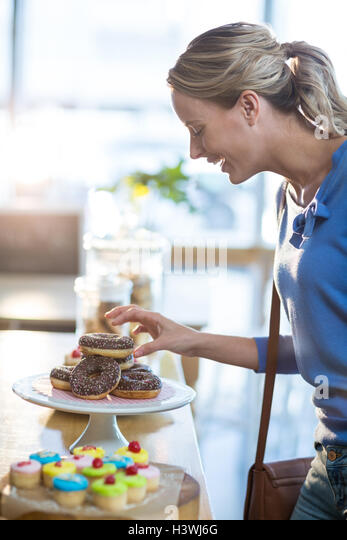 Excited woman selecting doughnuts from cake stand - Stock Image