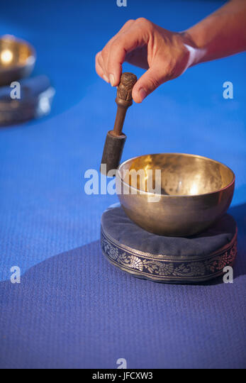 Hand with Clapper on the Bowl - Stock Image
