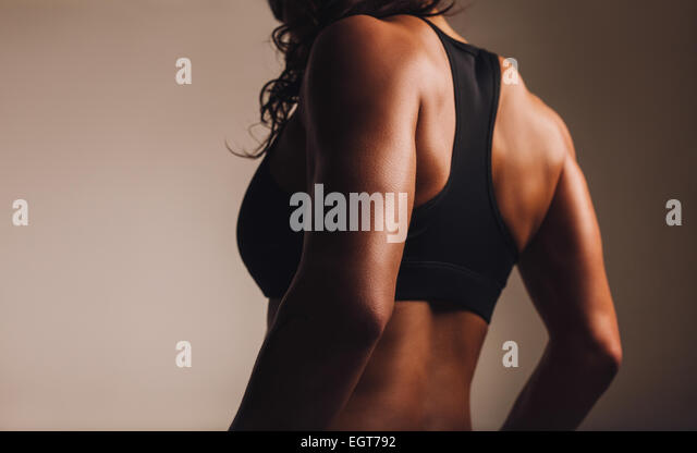 Back of a fit and muscular woman athlete in sports bra. Rear view of fitness female with muscular body. Highlighted - Stock Image