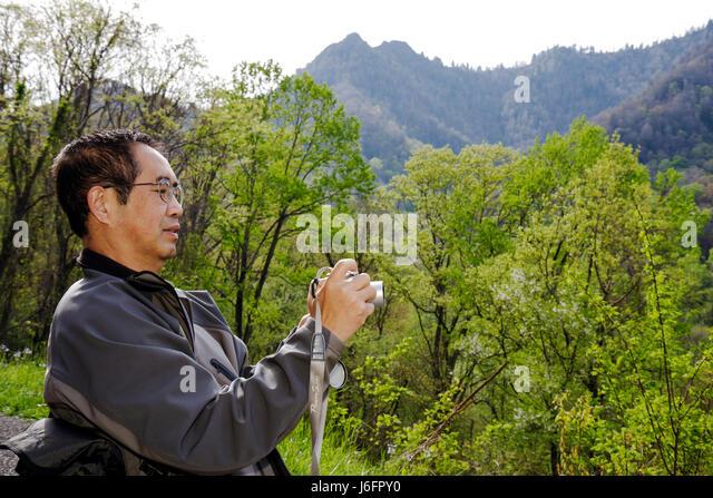 Tennessee Great Smoky Mountains National Park Asian man camera scenery ridge peak overlook Chimney Tops - Stock Image