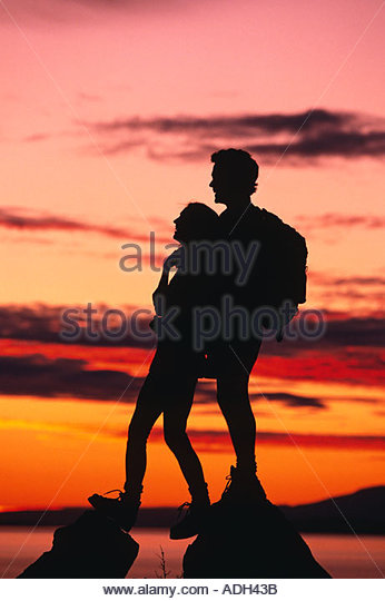 Couple Turnagain Arm Hiking Sunset Silhouette AK Southcentral Chugach State Park Summer - Stock Image