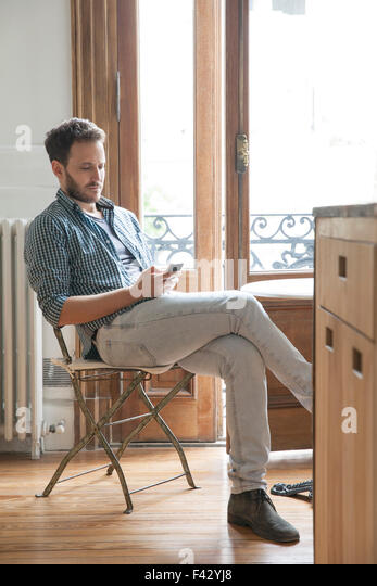 Man using smartphone at home - Stock-Bilder