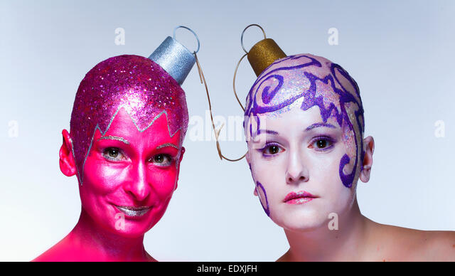 Two women with fantastic makeup posing as Christmas ornaments - Stock Image