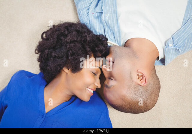 Peaceful couple lying on the floor - Stock Image