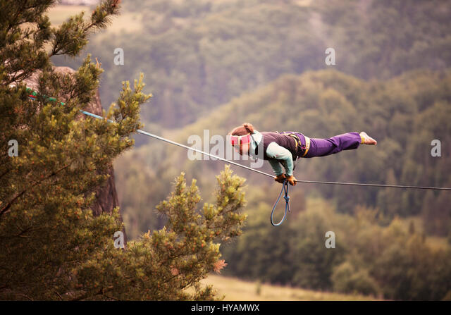 OSTROV, CZECH REPUBLIC: A female slackliner shows off on the high-wire. FROM DRESSING-UP in costume to hire-wire - Stock-Bilder