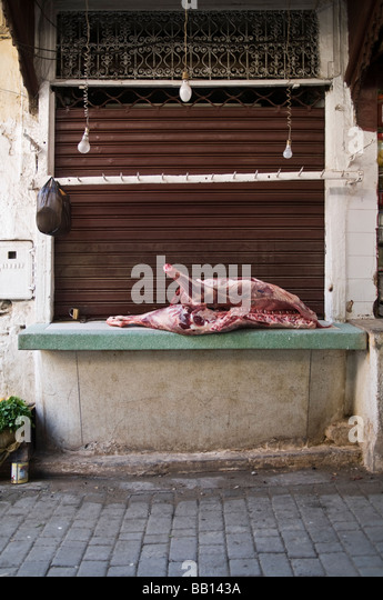 Closed butcher's shop with carcass left out on the counter to the elements. Not wrapped up, not chilled - Stock Image