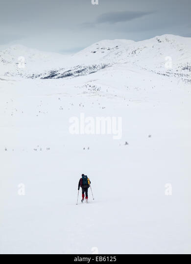 man  with heavy pack snowshoeing towards a  mountain top in a winter mountain landscape - Stock Image