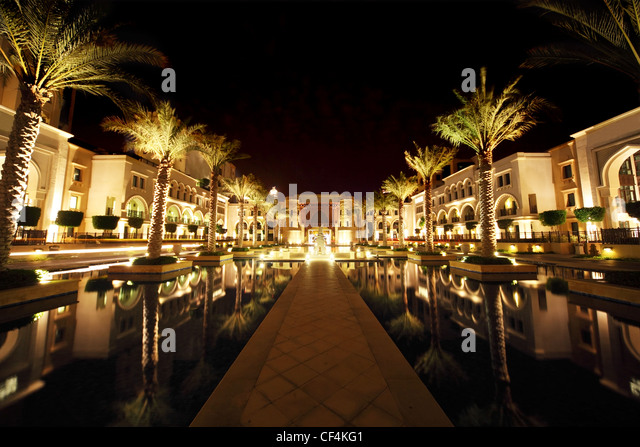 night Dubai street with palms and pool general view, United Arab Emirates - Stock Image