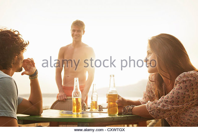 Friends having drinks together outdoors - Stock Image