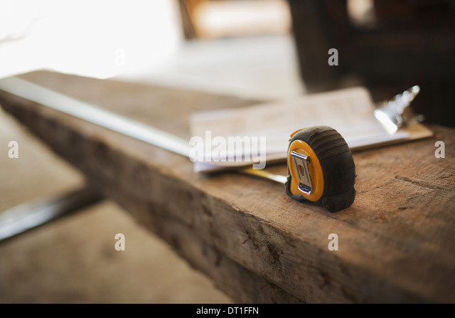 A reclaimed timber yard Recycled plank of wood measuring tape and a clipboard with paperwork - Stock Image