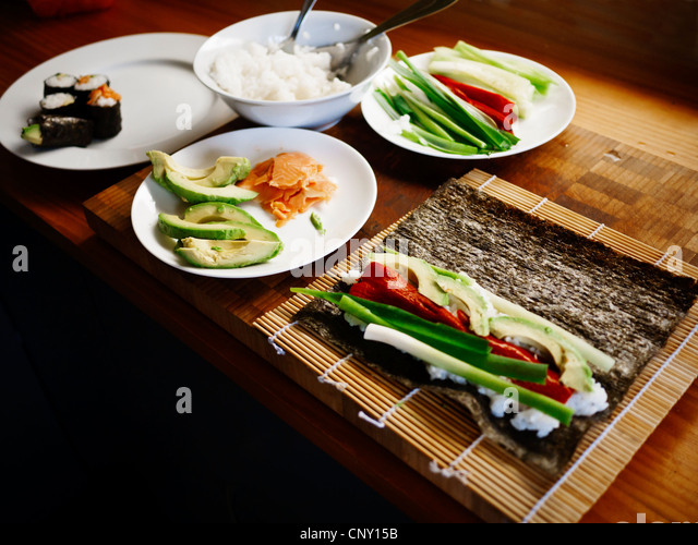 Making sushi at home: smoked salmon, red pepper, avocado, cucmber and spring onion. - Stock-Bilder