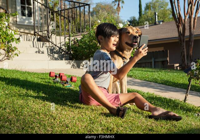 Boy posing for smartphone selfie with dog in garden - Stock Image