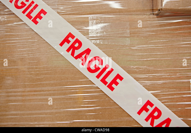 Cardboard box with parcel tape saying fragile - Stock Image