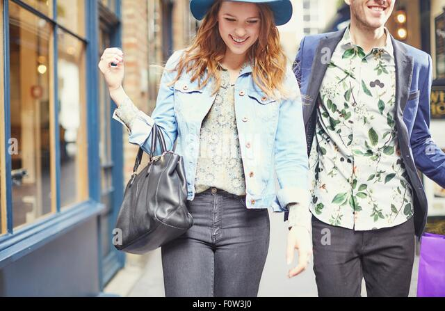 Cropped view of stylish couple out shopping, London, UK - Stock Image