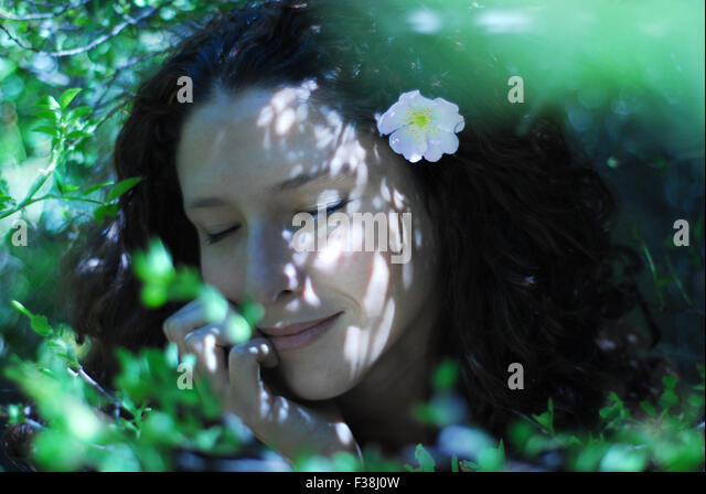 cute girl between a lot of green leaves with soft pink little flower in her curly hair - Stock Image