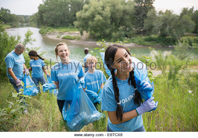 Volunteers carrying garbage bags in field - Stock Image