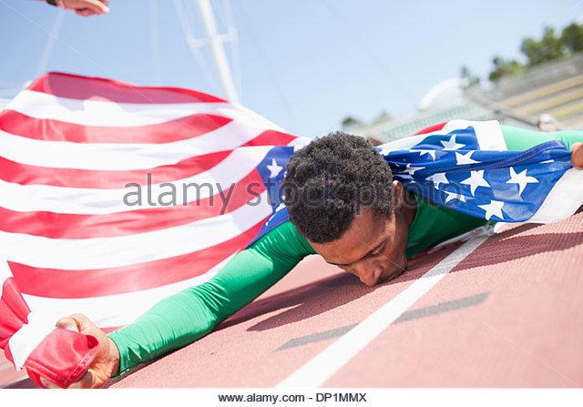 Runner celebrating on track with American flag - Stock-Bilder