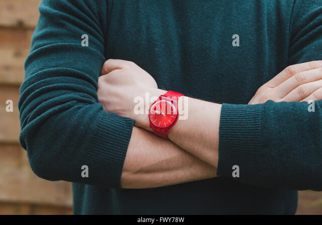 mens fashion, close up of hands of male wearing red watch and green pullover, style concept - Stock Image