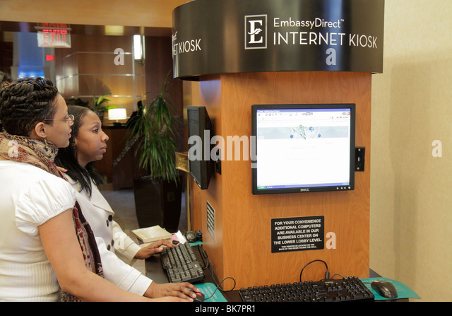 Washington DC 10th Street NW Embassy Suites Hotel lodging lobby Internet Kiosk Black woman keyboard screen guest - Stock Image