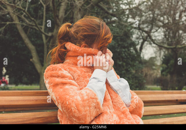 A young woman is sitting on a park bench and is wrapping up in her coat on a winter's day - Stock Image