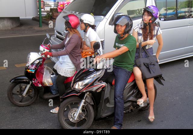 Thailand Bangkok Pathum Wan Rama 1 Road Asian man motorcycle motor scooter woman rider helmet - Stock Image