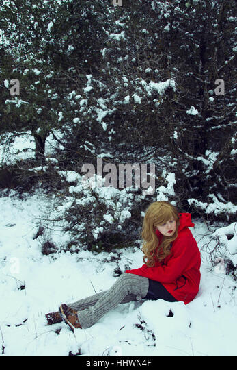 Young blond woman sitting and waiting in a snowy forest - Stock Image