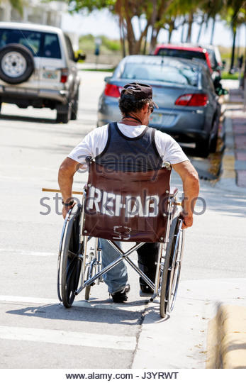 Miami Beach Florida man wheelchair handicapped disabled physically challenged rehab rehabilitation sidewalk street - Stock Image